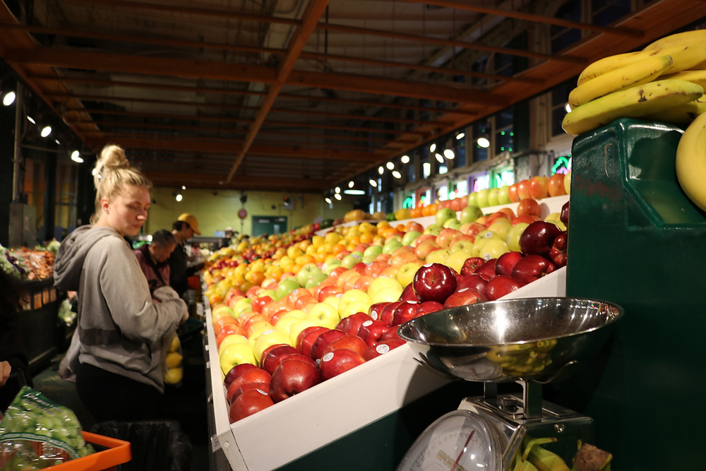 A woman looks at fruit in a supermarket. She's not wearing a mask.