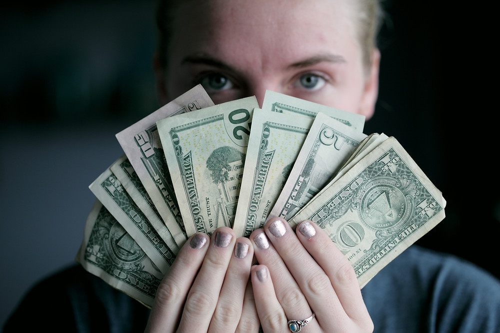 Woman holding up cash