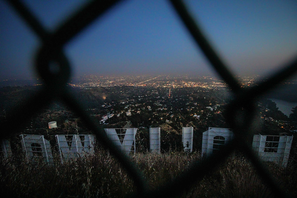 hollywood sign behind bars, overlooking the city at night