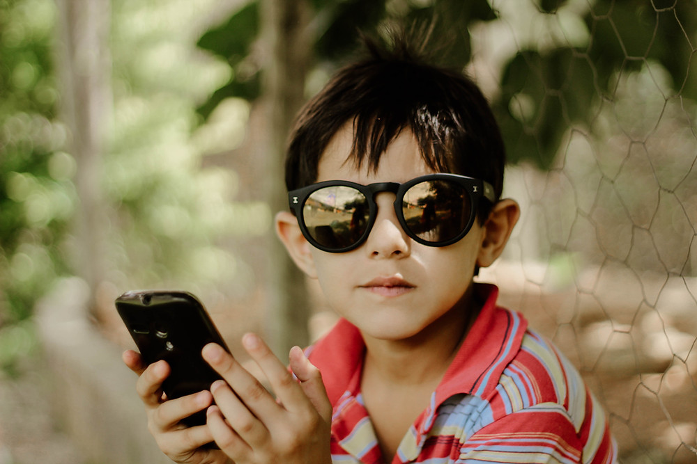 boy with sunglasses looking at his phone