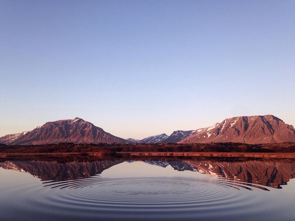 spiegelklarer See mit Bergen im Hintergrund