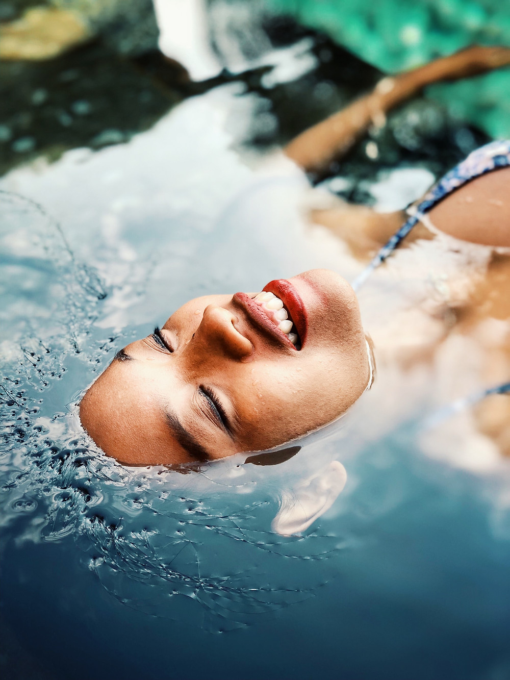 Brown skinned woman floating in water with a smile and happy