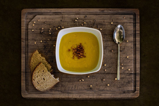Bowl of soup and bread on a wooden cutting board.Image by David Beneš