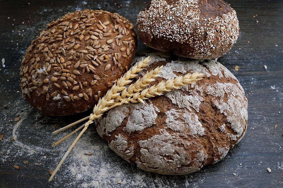 Pães sobre uma mesa de madeira com uma espiga de trigo