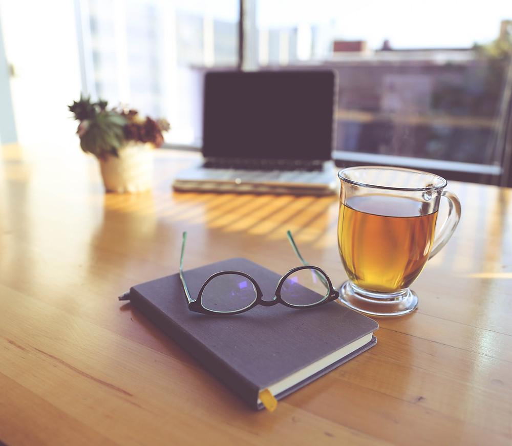 A mug of green tea, a book, and a laptop