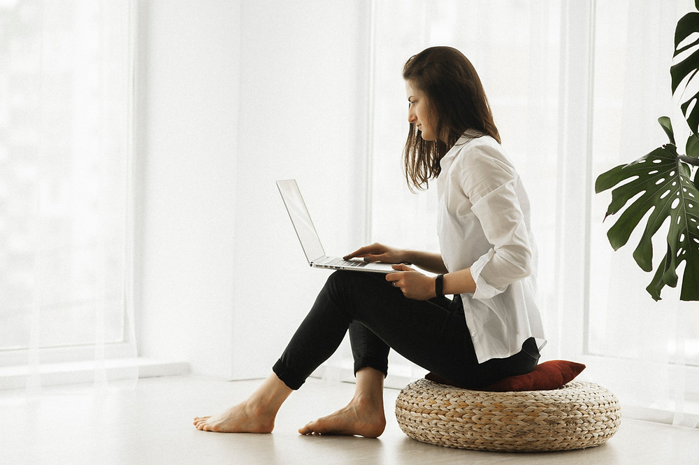 woman on floor pillow working on social designs through laptop