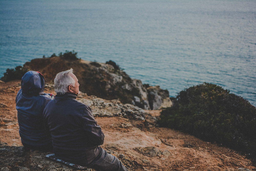 Elderly heterosexual couple looking out to sea on a cold day.
