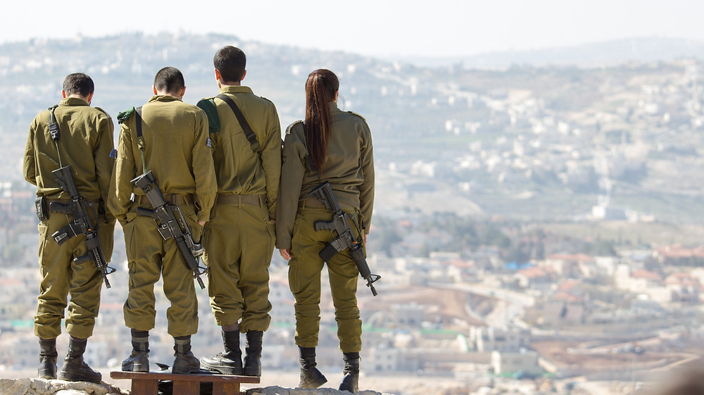 3 male uniformed IDF soldiers standing next to a a female IDF soldier overlooking a city