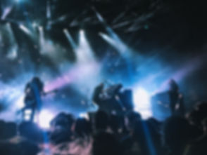 Live Concert Photo of an industrial band performing live on stage, using custom instruments, guitar, bass, and keyboard.