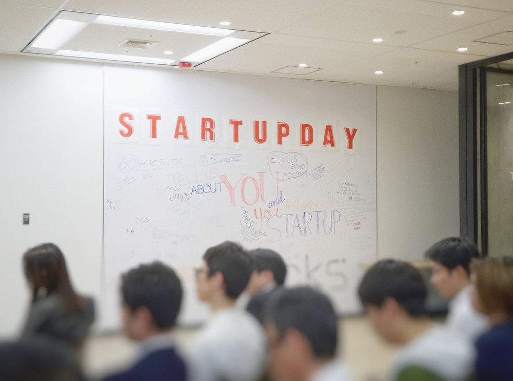 "A training room with delegates all looking towards the front of the room.  On the wall is a big whiteboard with the words ""Start Up Day"""