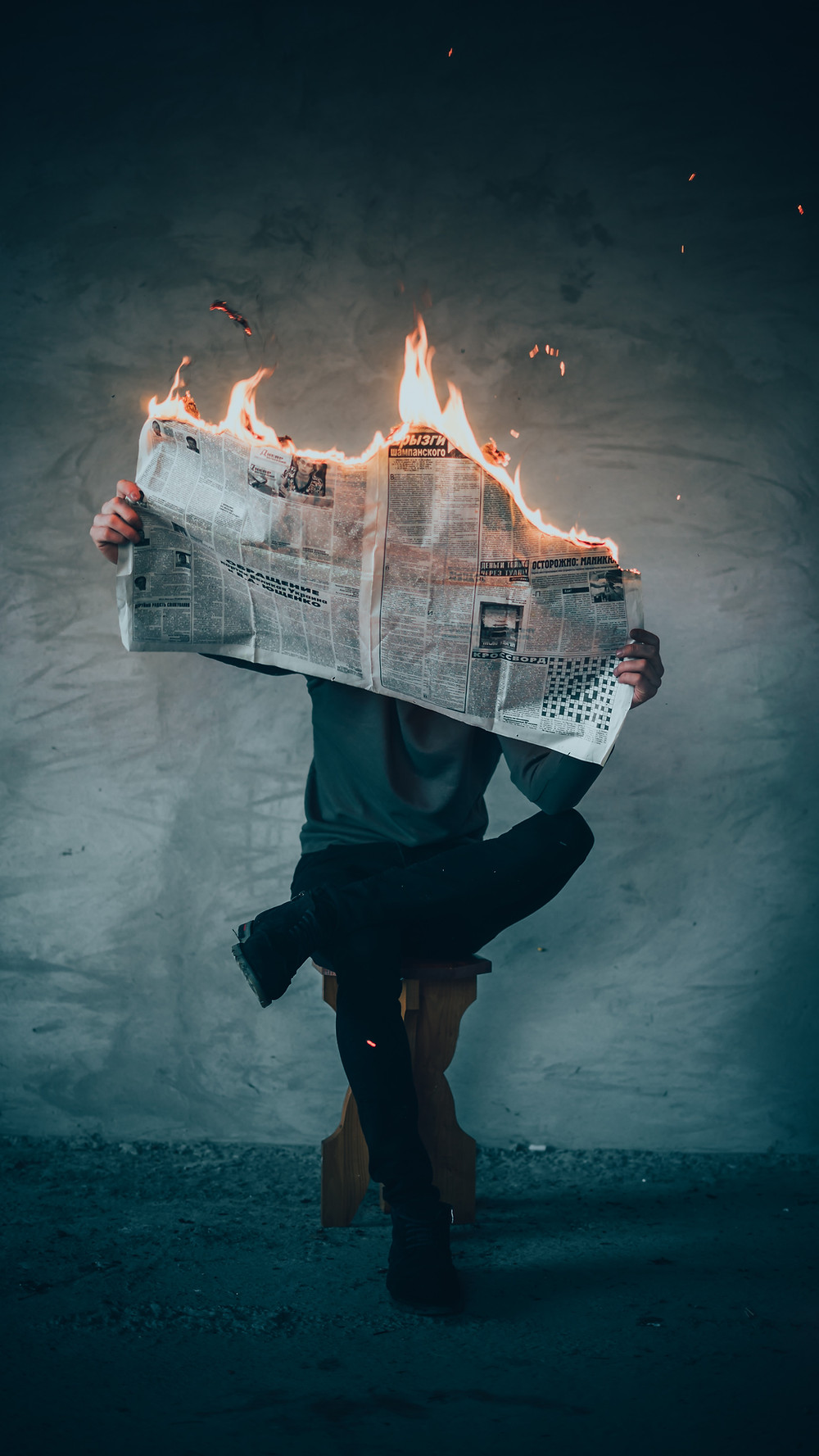 A person holds a newspaper as if to read it, but it's on fire.