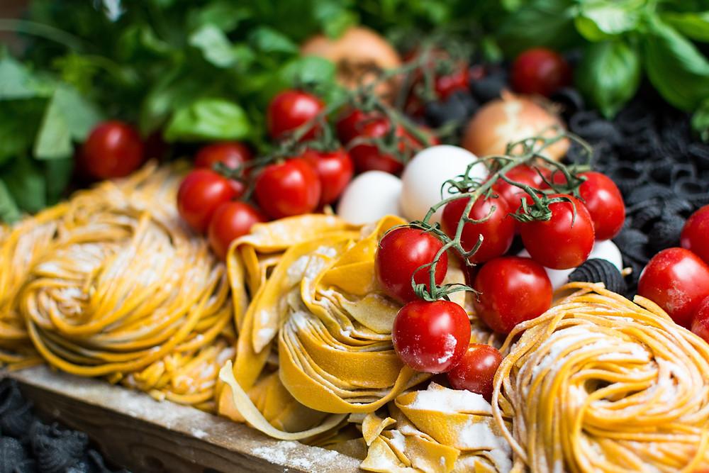 Imagem de diversos ingredientes italianos em destaque massa fresca e tomates cereja