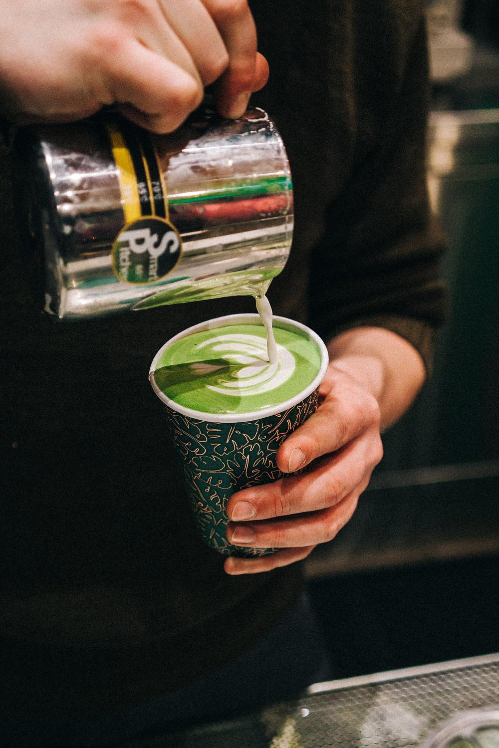 A barista prepares a matcha latte to go.