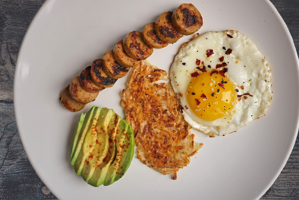 Eggs, avocado, hashbrowns and sausage.