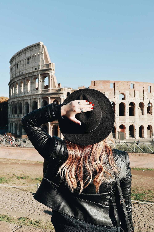 mulher segurando chapeu preto em frente ao coliseu