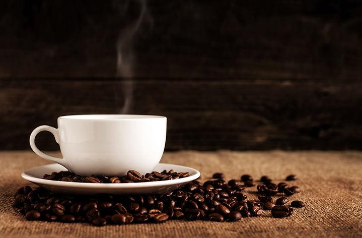Coffee mug with steam and coffee beans