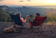 Avalanch seating - image of a couple sitting in camping chairs toasting a glass of wine, mountains in backdrop