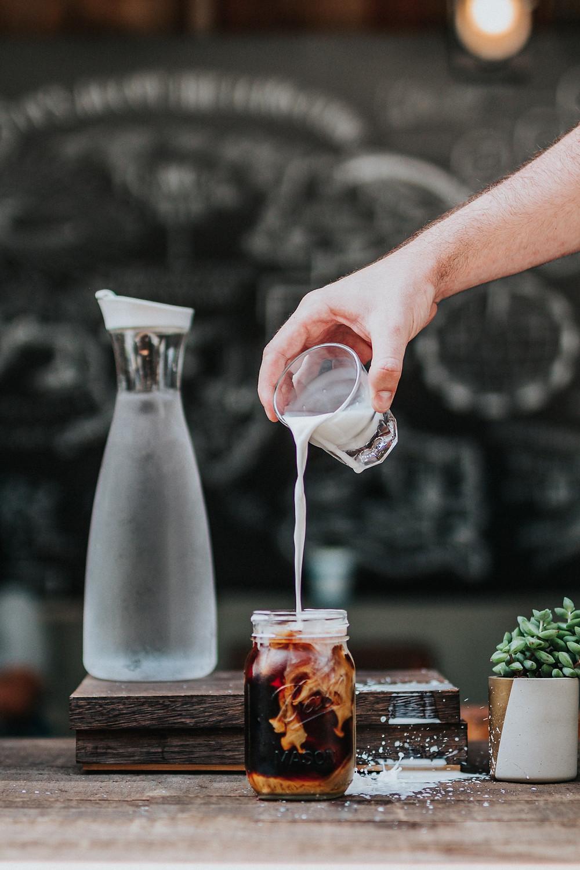ręka dolewa mleka do kawy z lodem
