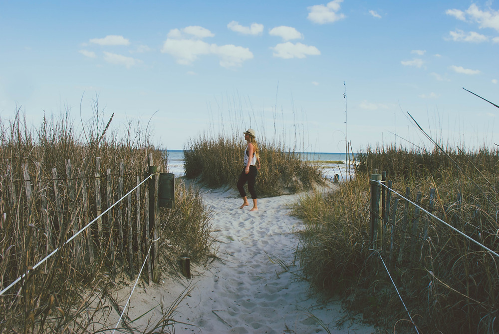 A woman walking in between the sand reeds on the beach at Myrtle Beach.
