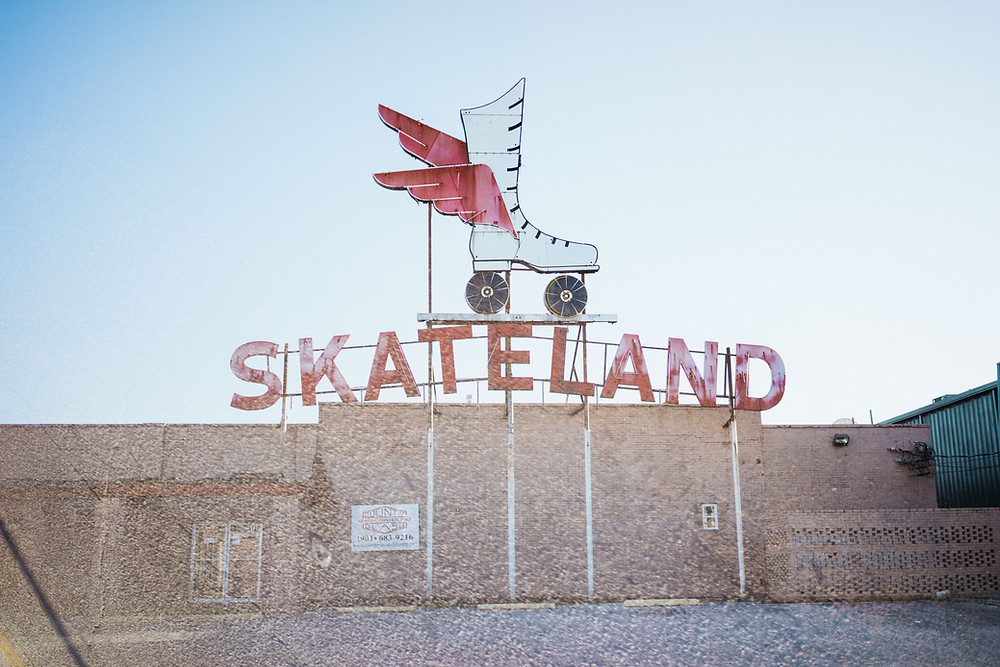 "A big sign advertising ""SkateLand"" includes a giant image of a skate with wings ."