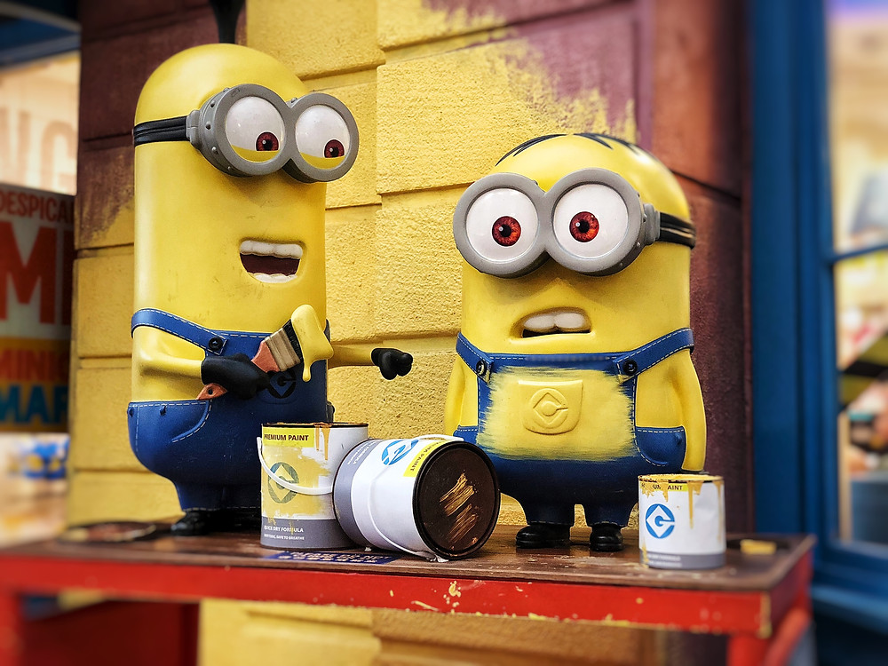 Two minions from the movie Despicable Me painting the facade of the building yellow.