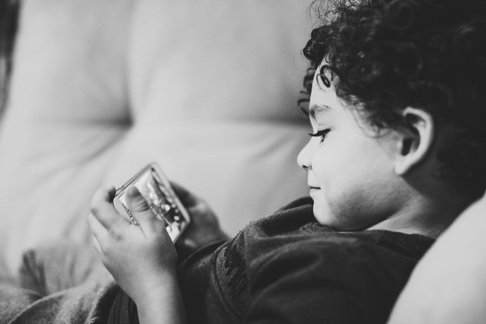 boy learning through play on an iphone device at home