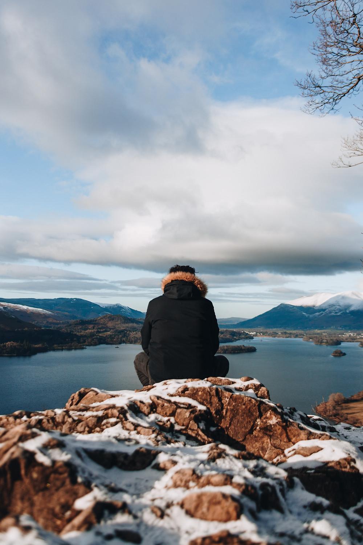 man sitting on snowy mountain watching peaceful lake
