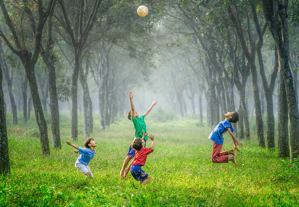 four children jumping in a lane of grass in between rows of trees.