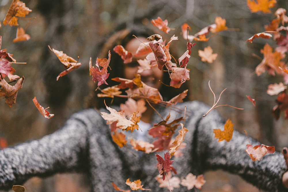 Woman throwing leaves in the air at fall time