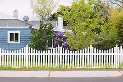 Pretty fence painted white. Bloomed trees. Blue house with a white chimney.