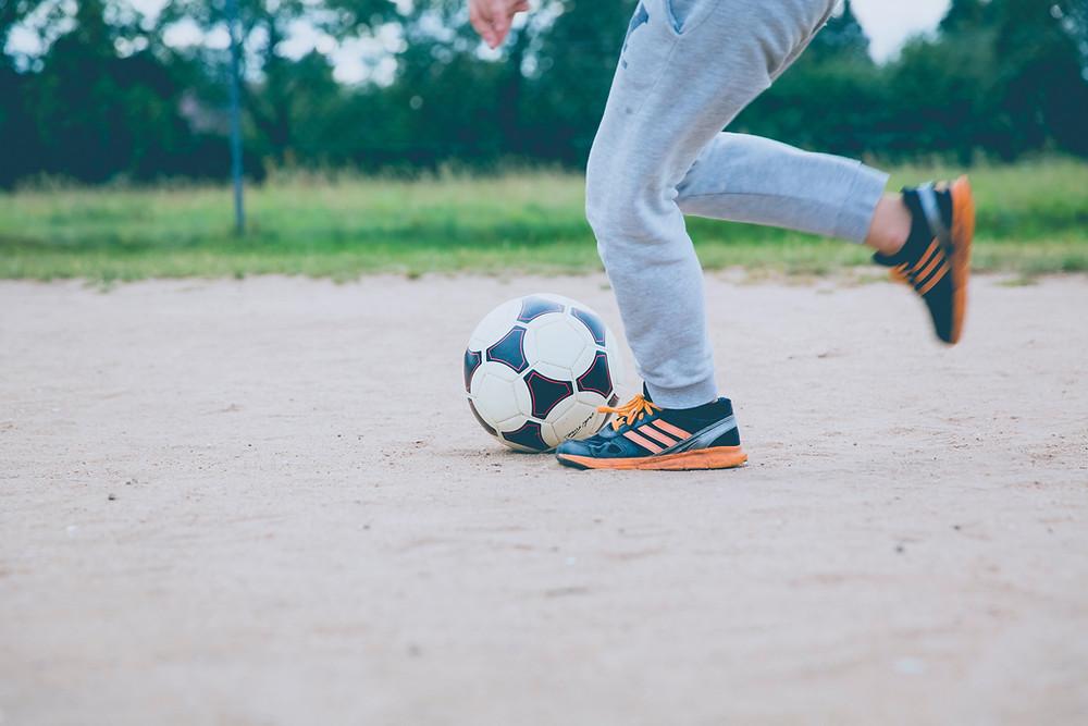 A boy kicking a football (soccer ball) on the sand