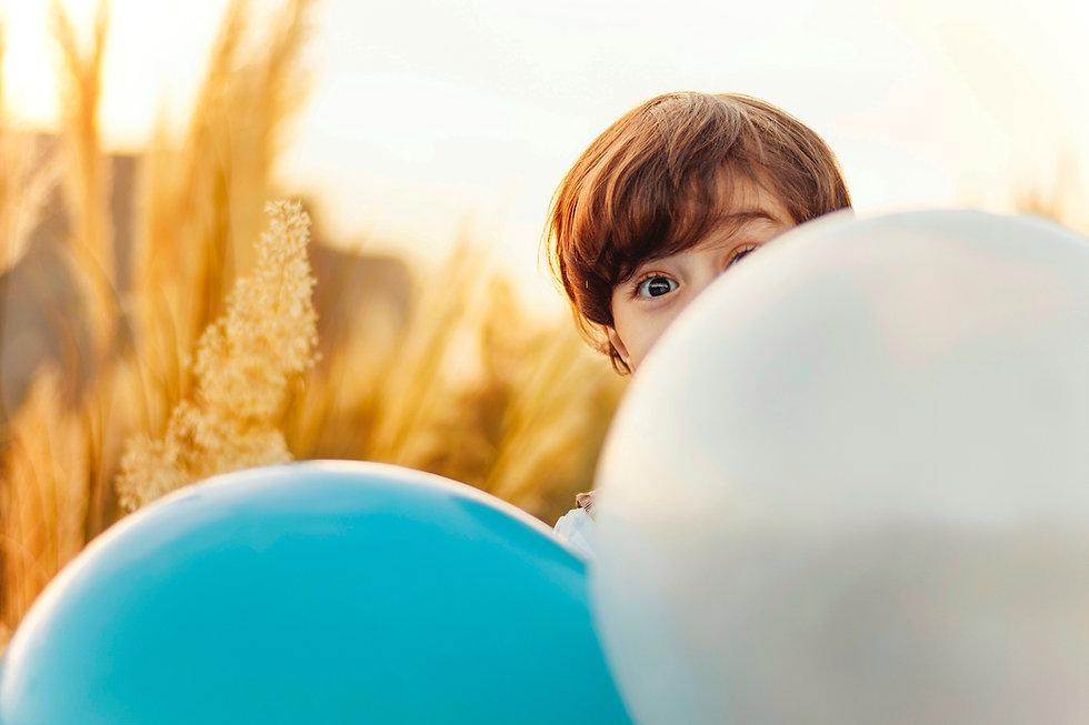 Kid behind balloons