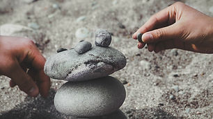 two hands working together to stack smooth grey pebbles on a sandy beach