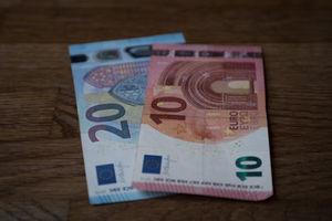 Geld auf einem Masivholztisch zur Verdeutlichung von günstigen Preisen