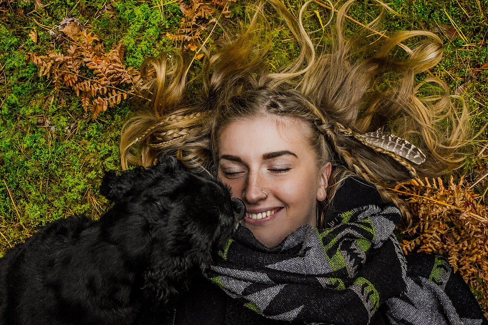 A happy girl lying down in nature with a beautiful smile. - The Guiding Voice
