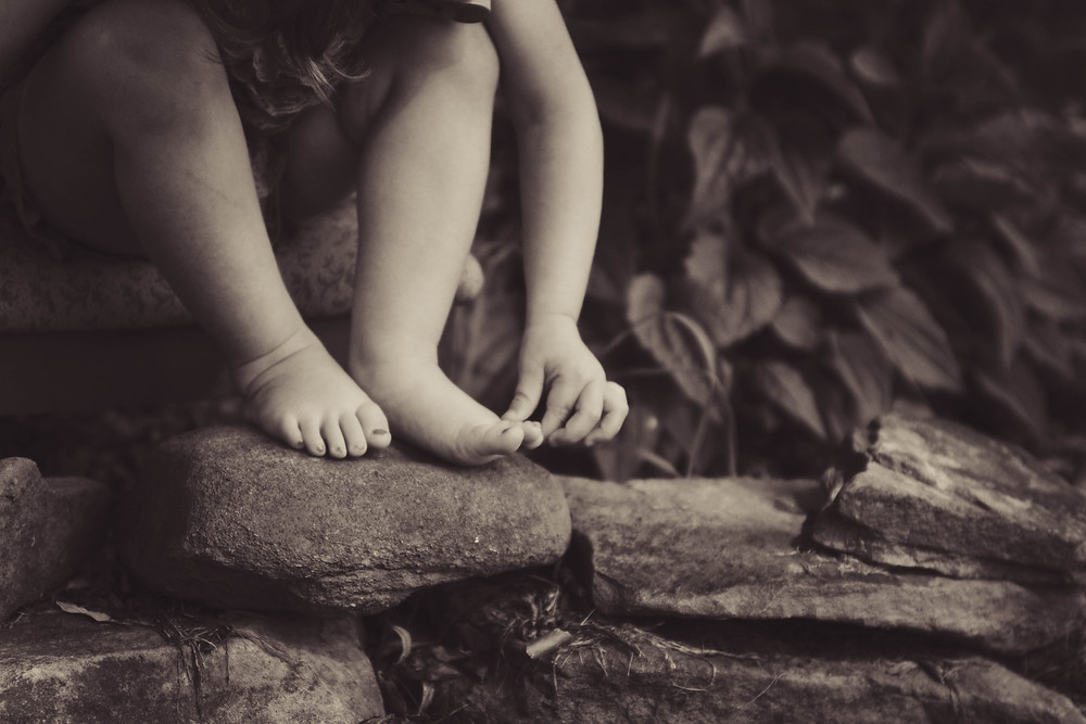 A little girl sitting with her bare feet on a rock
