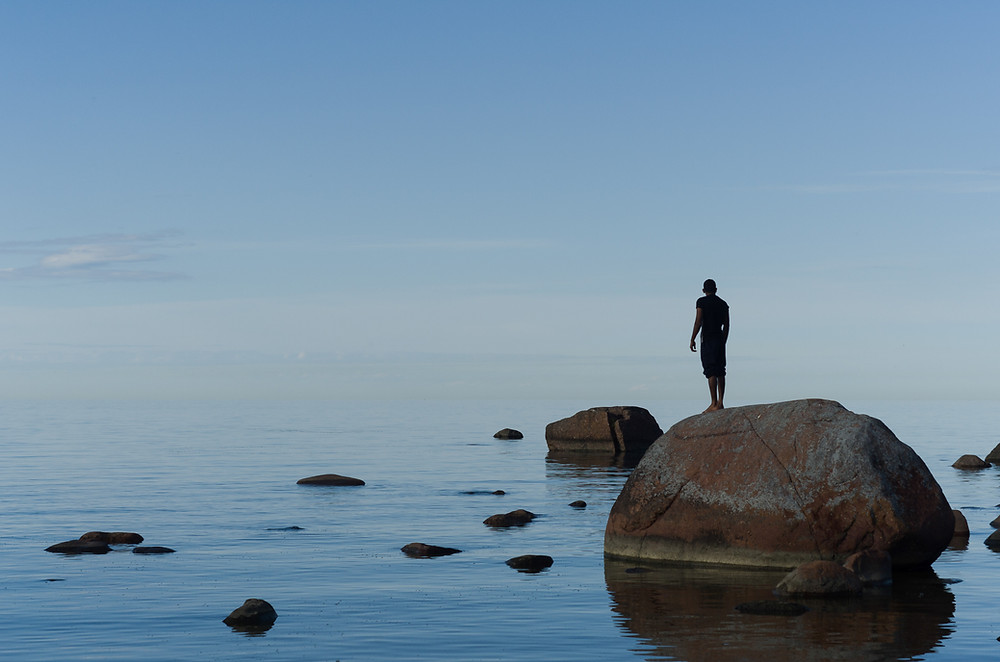 A man stands, seemingly lost, on a rock in the middle of the sea. This is how it might feel to be overwhelmed by emotions.