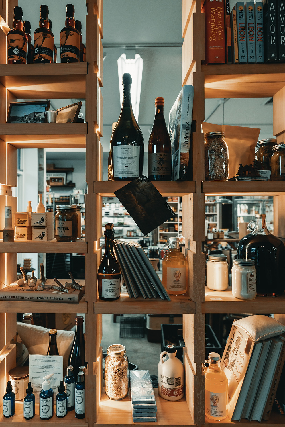 Backless Wooden Shelfs in a Retail Store with Interesting Bottles, Books and Pictures for sale