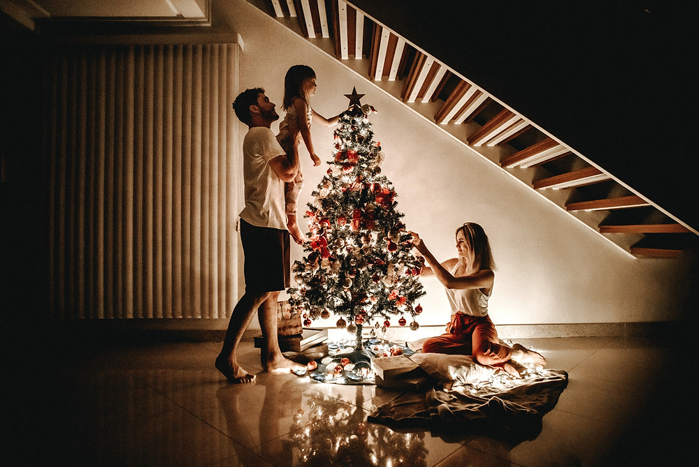A family decorating their tree at Christmas, getting through the holidays with grief. Grief counseling can help you with grief and loss on the holidays and other significant days. Marble Wellness, a counseling clinic in Ballwin, MO can help.
