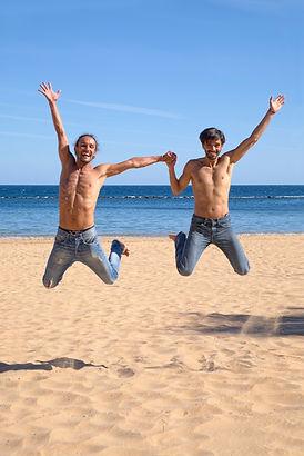 Gay men jumping on beach