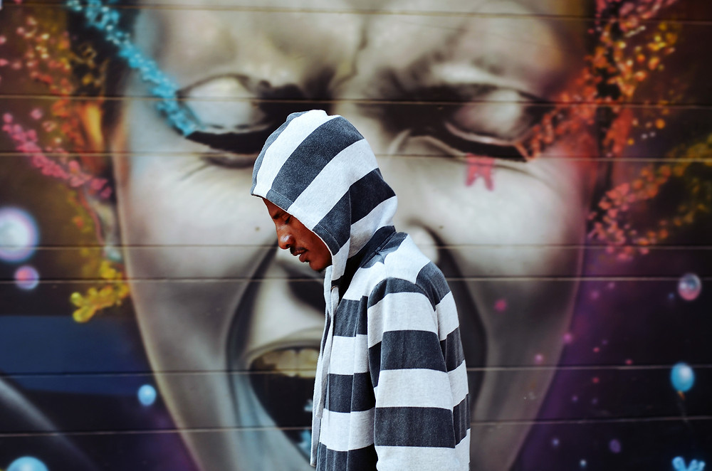 A man in a striped hoodie walking past a face graffitied on a wall