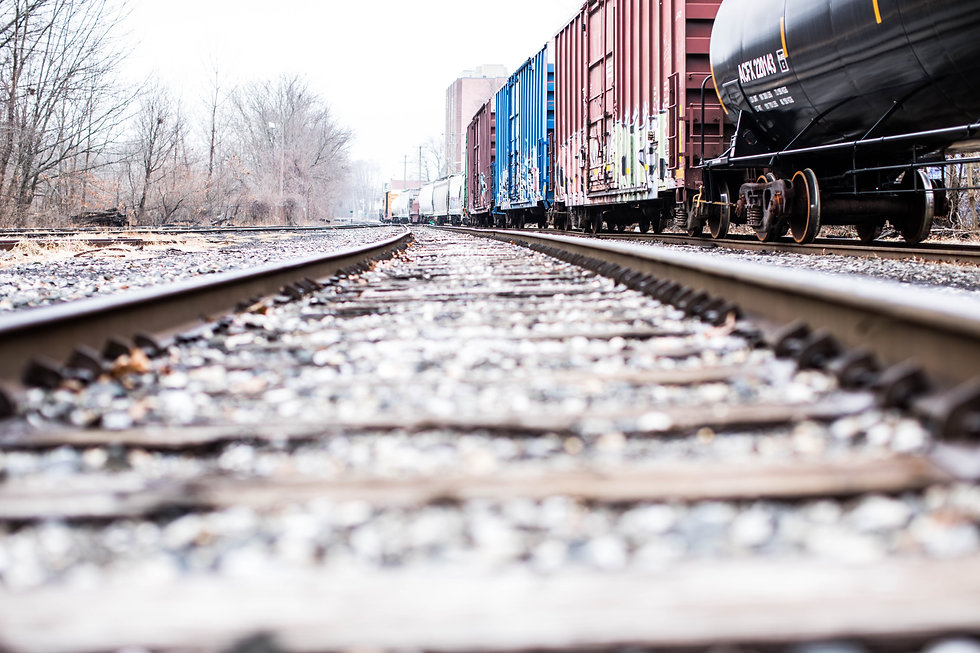 Close up image of rail tracks with a line of hopper and tank cars out of focus.