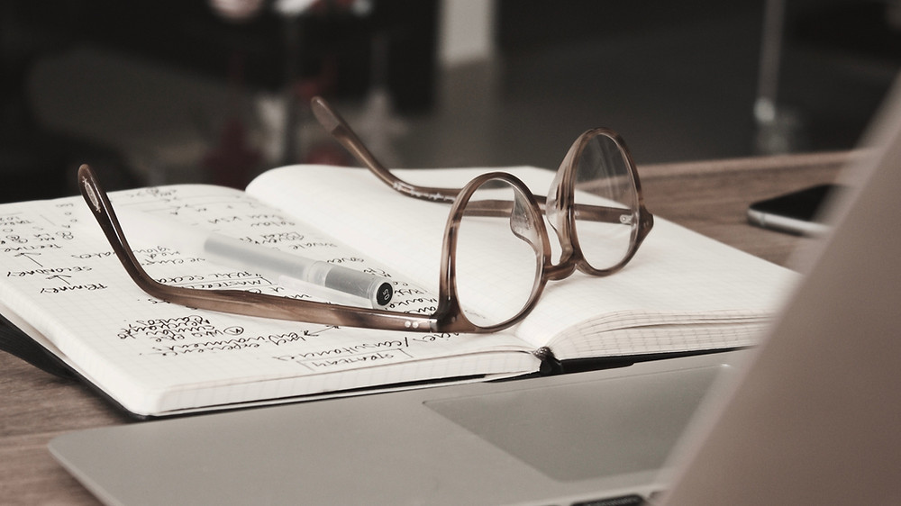 Notebook open with eye glasses on top