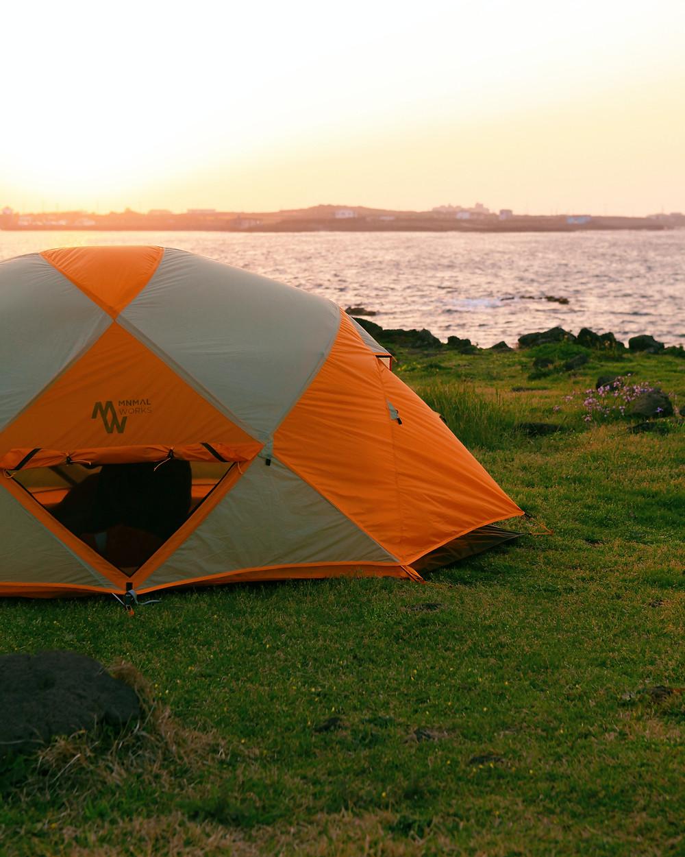 Orange and gray Mnmal Works Tent in coastal field near the shoreline under setting sun