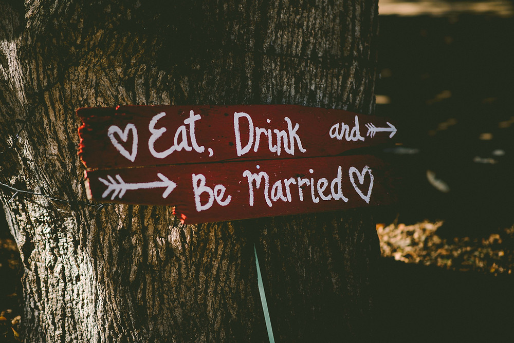 Wedding sign on tree, eat, drink and be married.