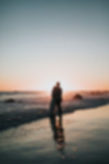 Image by Nathan Dumlao of a couple standing by the seashore at sunset hugging