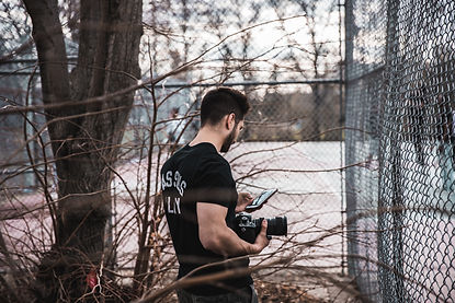 FIlmmaker and photographer standing outside at a sporting court filming and checking a shotlist on his phone.