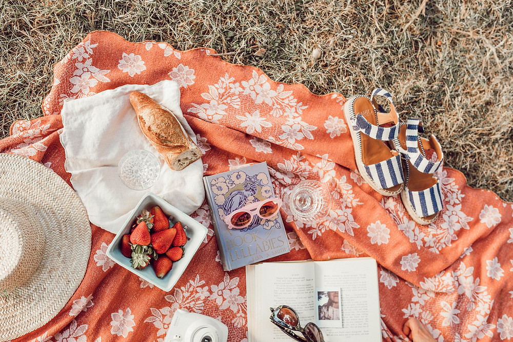 picnic blanket with sandals, hat, strawberries, sunglasses and book