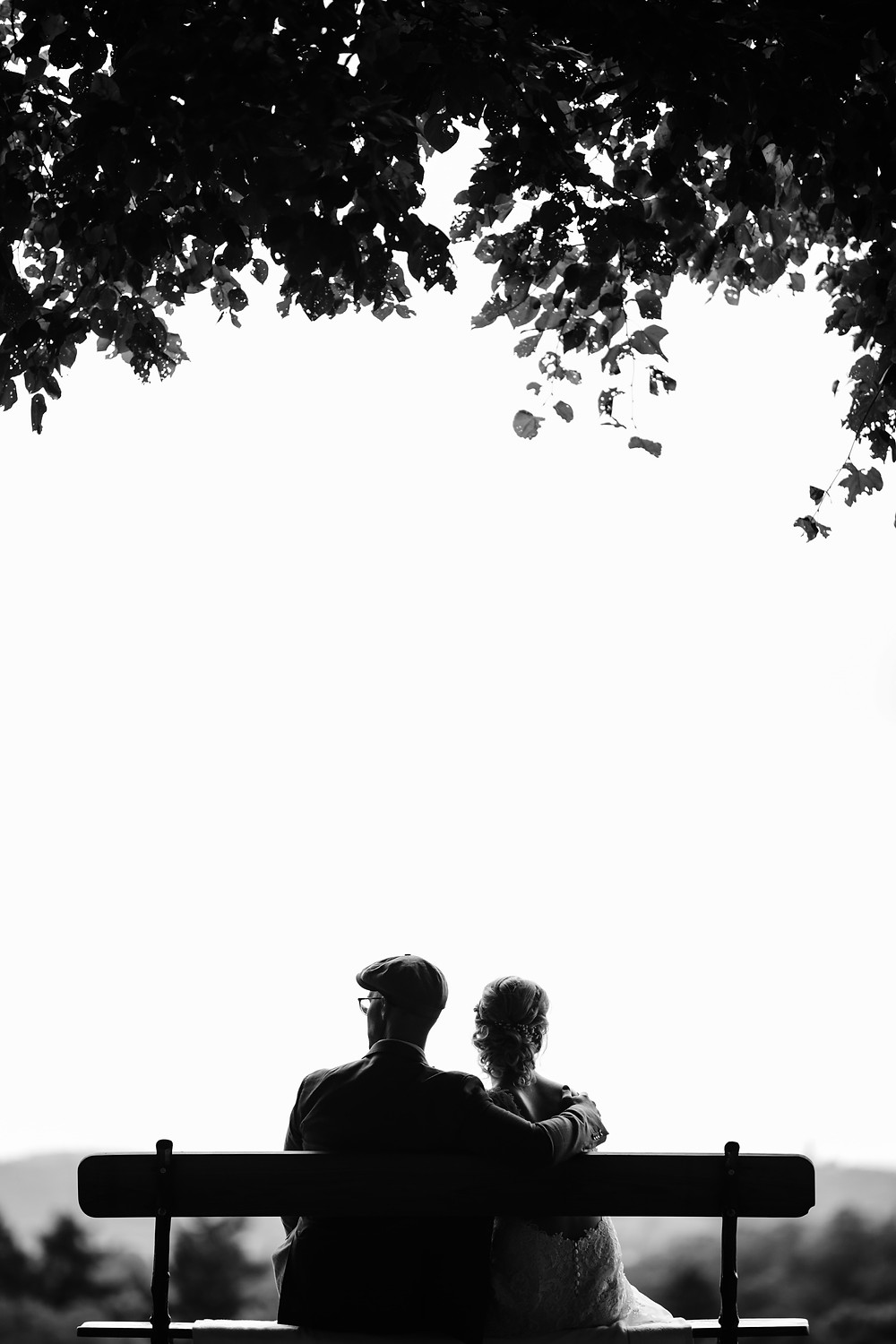 black and white photo of a couple sitting on a park bench