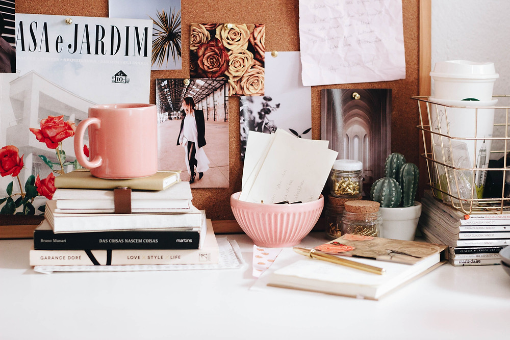 A desk featuring pink accessories and books